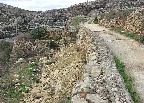 Construction rubble dumped into garigue at Mgarr is-Xini