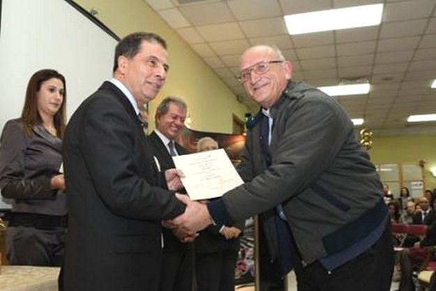 Canon Mario Cassar receives certificate in awards ceremony