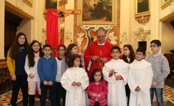 Fr Joe Caruana distributes symbols to children in Passion celebration