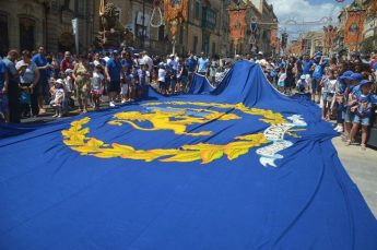 Children parade with giant flag bearing the Leone Band coat of arms